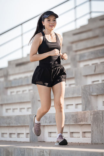 Full length of young woman standing against staircase
