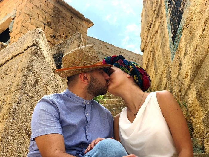Low Angle View Of Couple Kissing Against Old Building