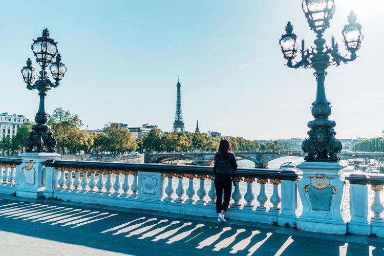 Full length of woman standing on bridge against clear sky