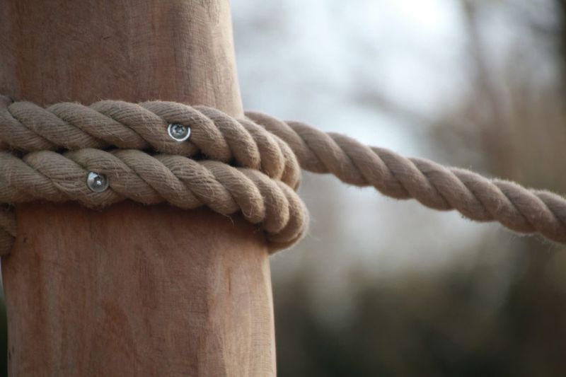 Close-up of rope rolled up on wood