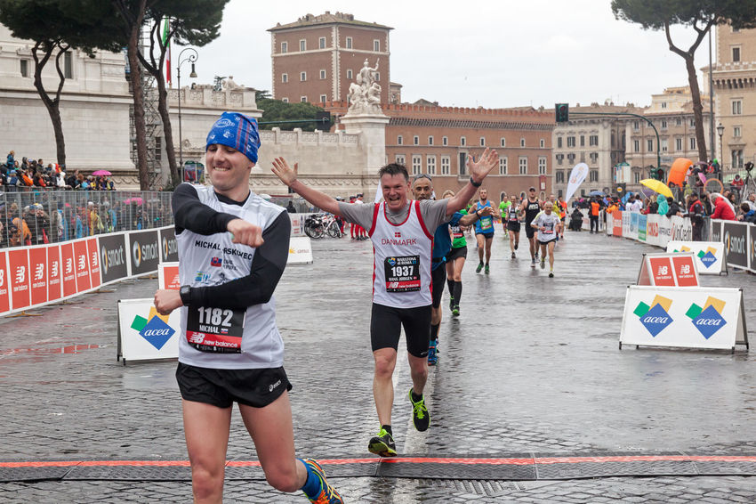 Rome, Italy - March 22, 2015: Some participants in the twenty-first Rome Marathon on arrival at the finish line after a run in the rain. Arrival Athlete Atletic Competition Day Finish Line  Happiness Italy Joy Marathon Outdoors Rain Rome Runners Running Street Street Running Urban Water