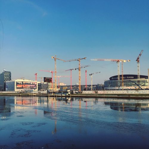 Cranes at construction site in city against clear blue sky