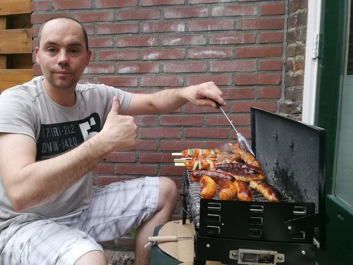 Portrait of mid adult man showing thumbs up while preparing food on barbeque grill at yard