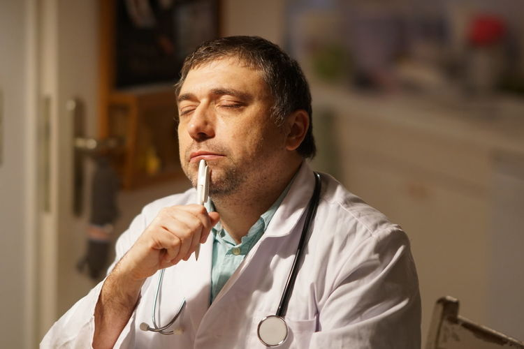 Thoughtful Mature Doctor With Pen Sitting In Hospital
