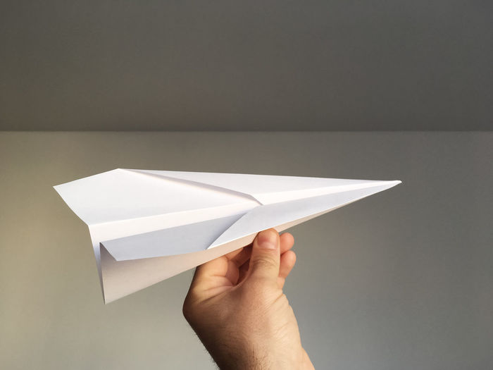Midsection Of Person Holding Model Airplane Against White Wall