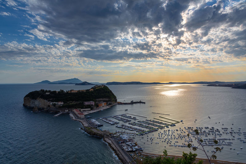 High angle view of bay against sky at sunset