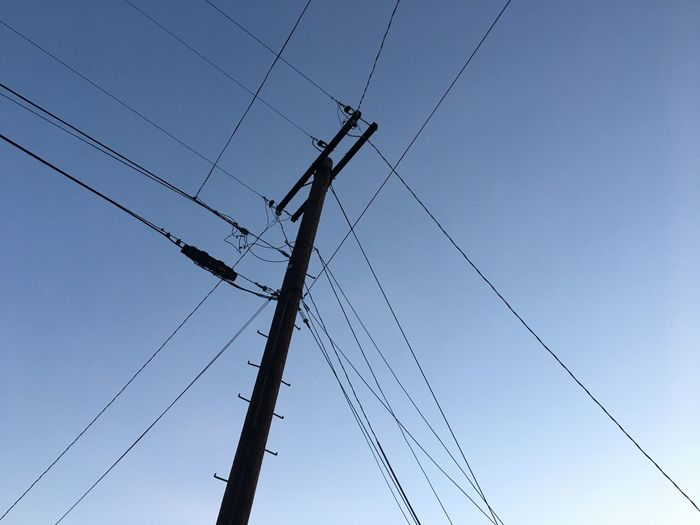 Low Angle View Of Telephone Line Against Clear Blue Sky