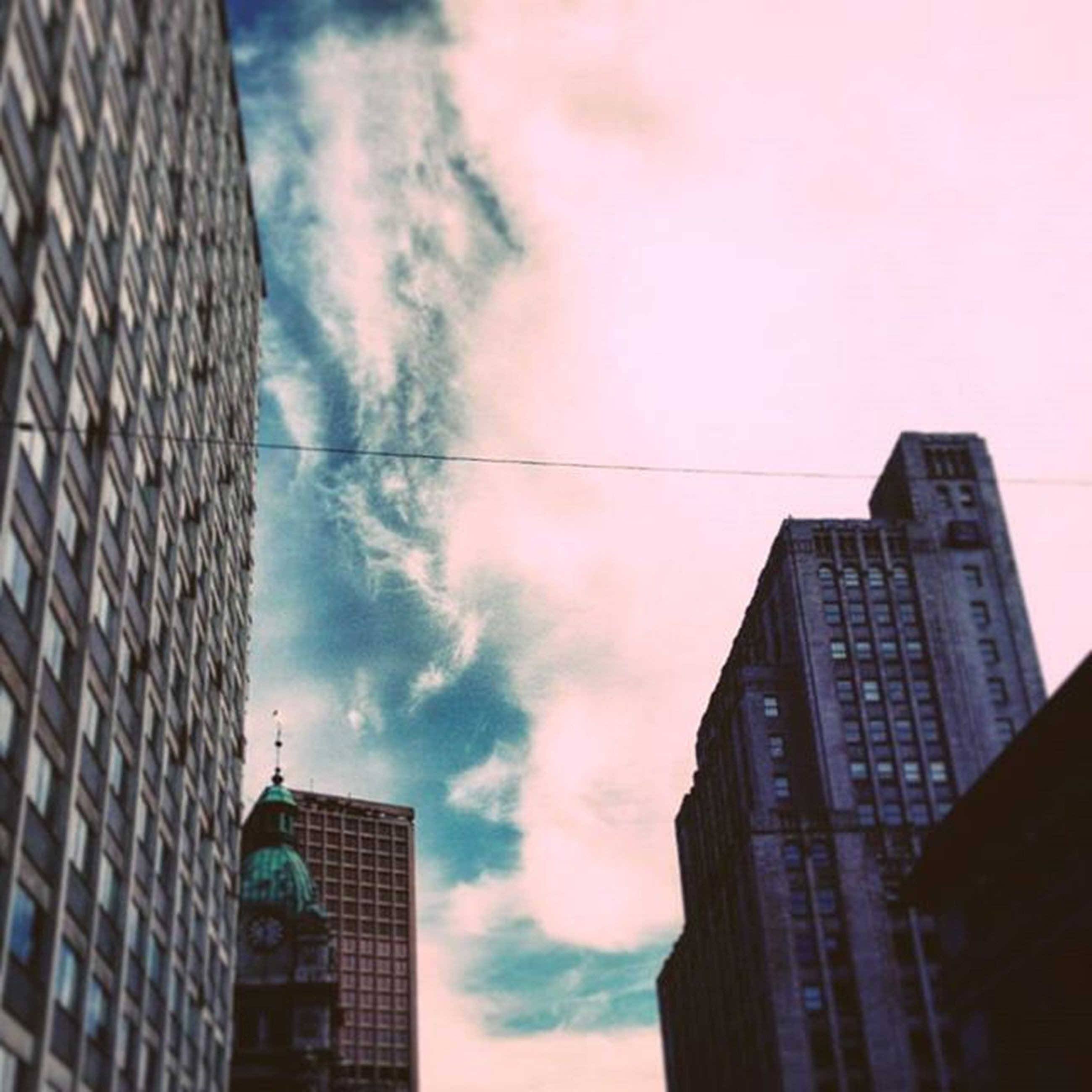 building exterior, architecture, built structure, low angle view, city, sky, skyscraper, cloud - sky, building, office building, modern, tall - high, cloudy, tower, cloud, residential building, outdoors, silhouette, glass - material, no people