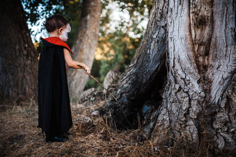 Side view of woman standing by tree trunk in forest