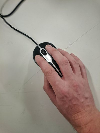 Cropped Hand Of Person Using Computer Mouse On Desk In Office