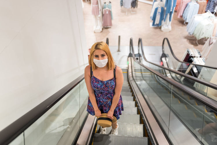 Portrait of a young woman standing on escalator