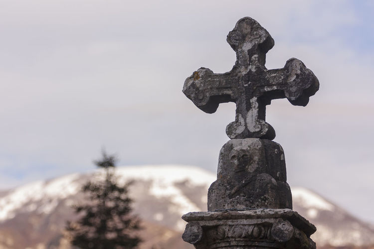 Close-up of cross sculpture against sky