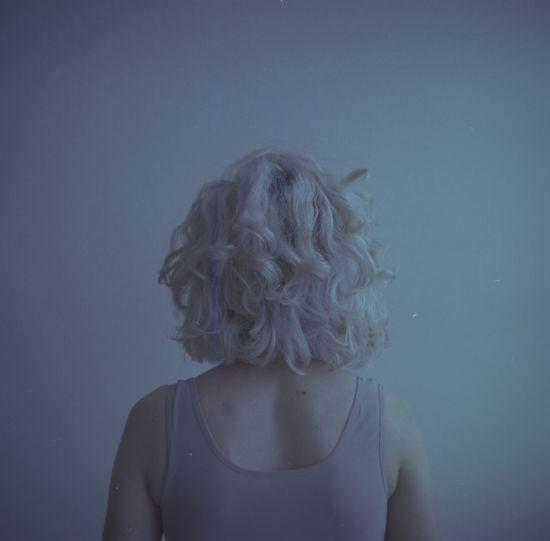 Portrait of woman against blue background