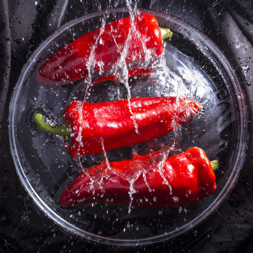 Close-Up Of Red Chili Peppers Falling In Water