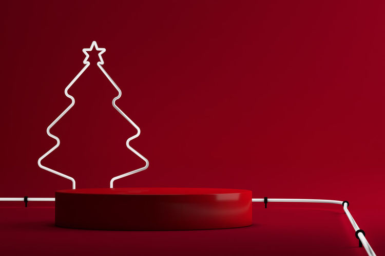 Close-up of illuminated electric lamp against red background