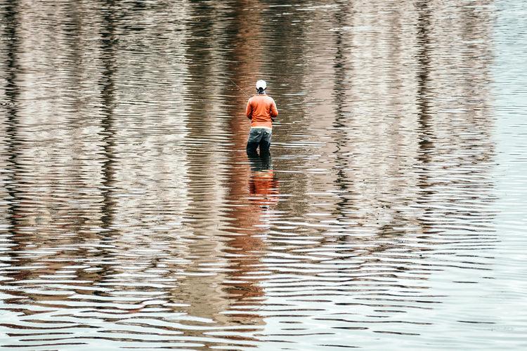 Rear view of man fishing in sea