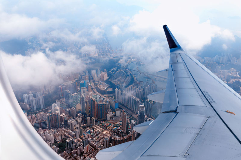 Plane to hong kong. airplane window view at the skyscrapers. overhead city view. cityscape aerial.