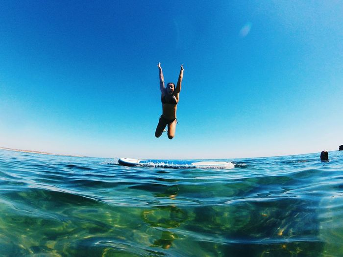 Woman jumping in sea against clear blue sky