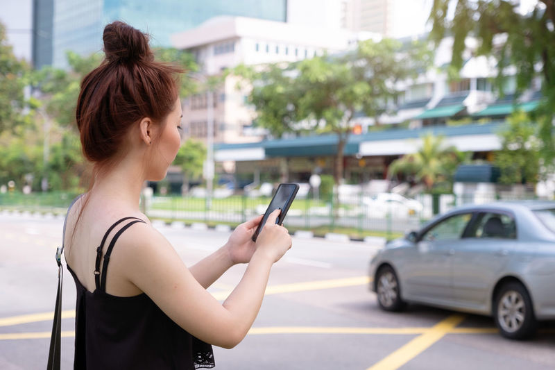 Side view of woman using mobile phone on street