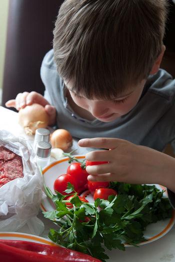 Boy with kebab ingredients on plate