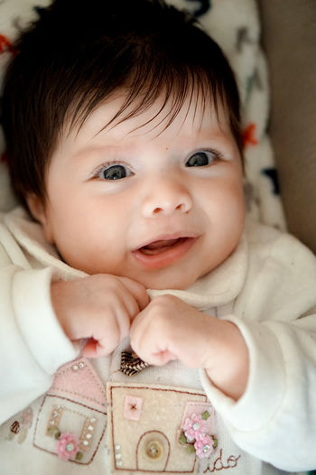 Close-Up Portrait Of Cute Baby Girl At Home