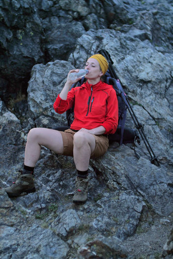 female hiker drinking water Alpine Backpacking Boots Camping Expedition Freedom Hiking Hydration Travel Trekking Woman Active Activity Adventure Backpack Bottle Caucasian Clothing Day Drinking Female Fitness Front View Full Length Healthy Lifestyle Holding Leisure Activity Lifestyles Nature One Person Outdoors People Real People Rock Rock - Object Solid Sport Trail Water Young Adult