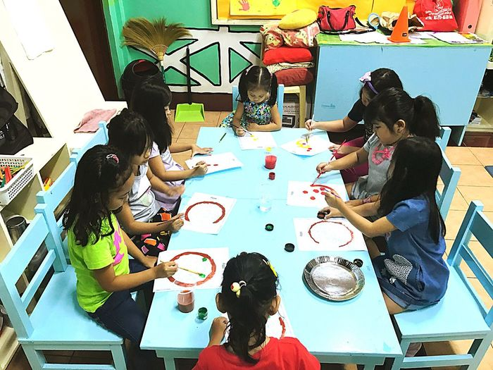 These Pre schoolers are attending a one week program in a school during a summer is to see how ready they are for the incoming school task for this day is to color a pizza pie according to the pictures they can see inside the and objects hey they have their own story to tell.#painting 🙂 Group Of People Indoors  High Angle View Real People Table Sitting The Photojournalist - 2018 EyeEm Awards Togetherness Communication Creativity Friendship