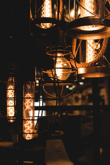 Close-Up Of Illuminated Light Bulb Hanging At Night