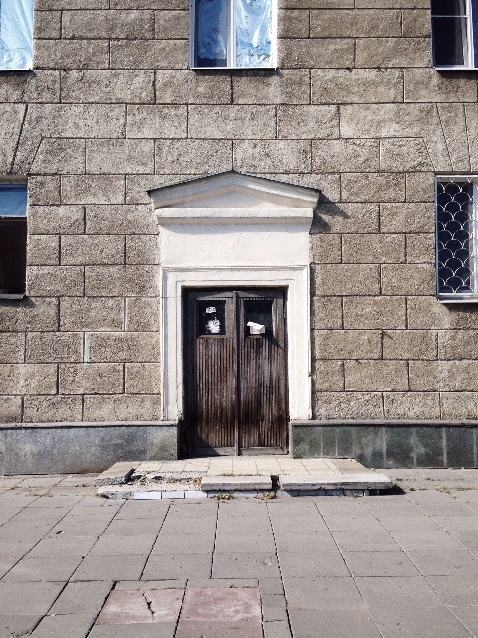 architecture, building exterior, built structure, window, brick wall, door, cobblestone, entrance, wall - building feature, house, building, facade, residential structure, stone wall, closed, residential building, sidewalk, day, wall, sunlight