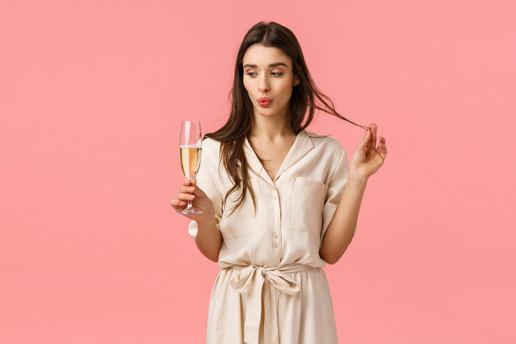 Portrait of a beautiful young woman drinking against red background
