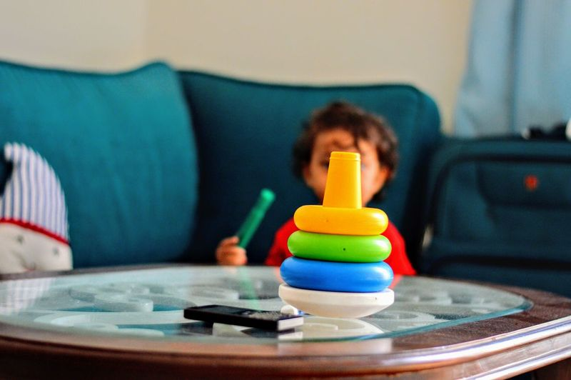 Boy With Stacked Colorful Toys At Table In Home