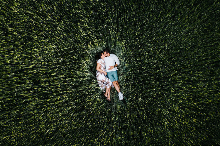 High angle view of man and woman standing in grass