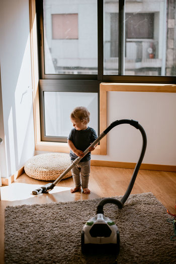 Full length of baby boy cleaning floor
