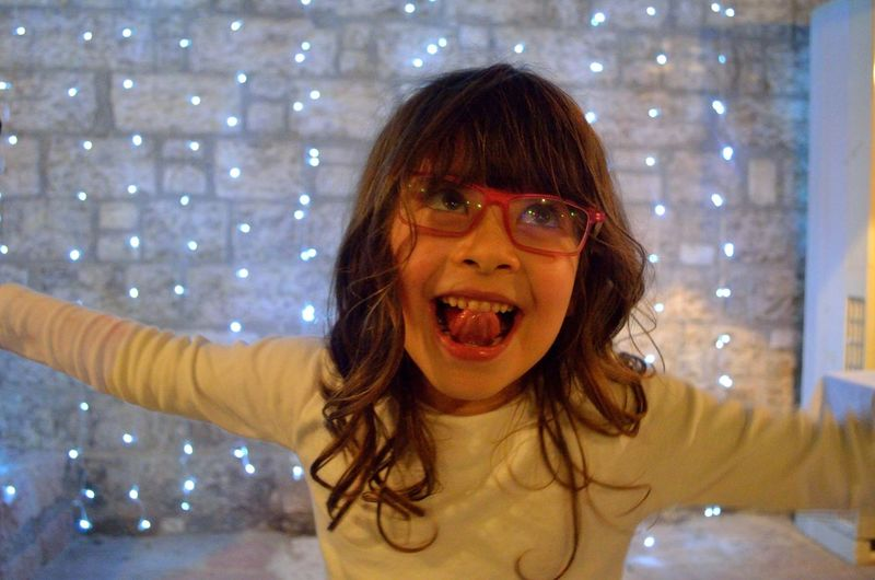 Close-Up Of Happy Girl Against Illuminated Lights On Wall