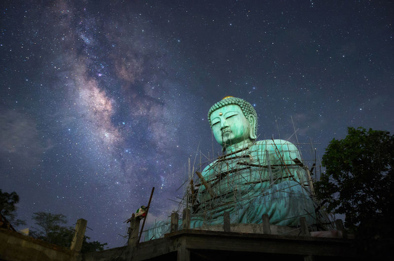 Giant buddha with milky way in sky at night, mae tha district, lampang province