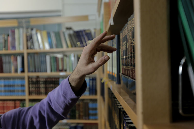 Cropped hand of man touching book in shelf