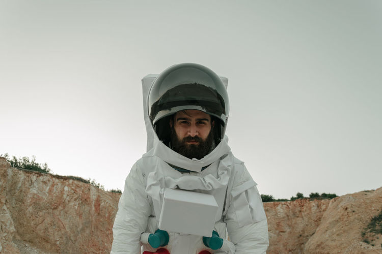 Low angle portrait of male astronaut standing on field against sky