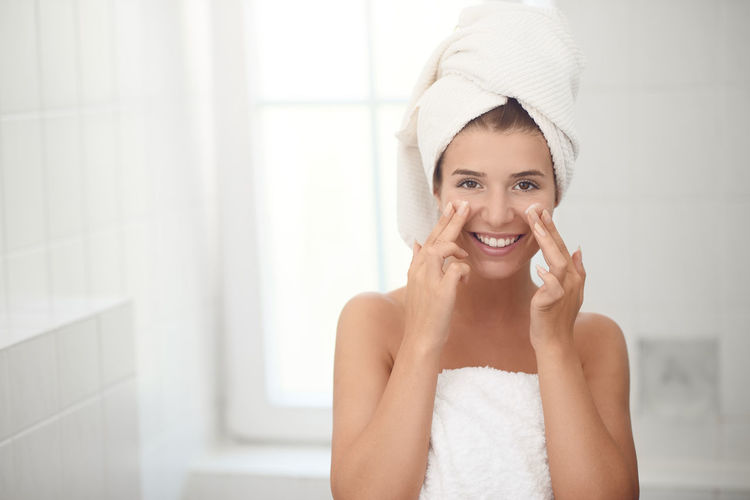 Happy young woman applying skin lotion Skin Care Smiling Happiness Towel Looking At Camera Portrait One Person Body Care Beauty Young Adult Indoors  Beautiful Woman Wrapped In A Towel Woman Face Aging Aging Process Applying Lotion Moisturizer Copy Space Bathroom Domestic Bathroom Hygiene Hair Teeth Front View