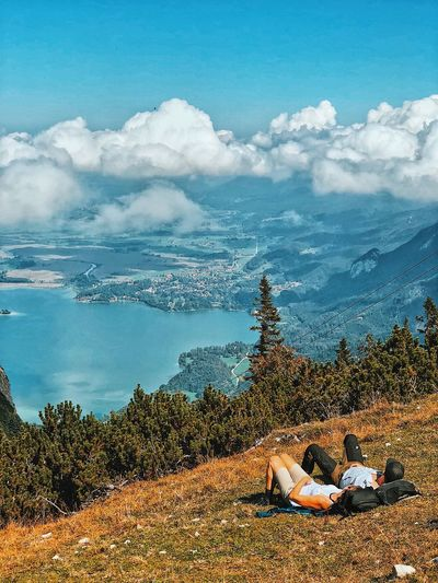 High angle view of couple lying on mountain against cloudy sky