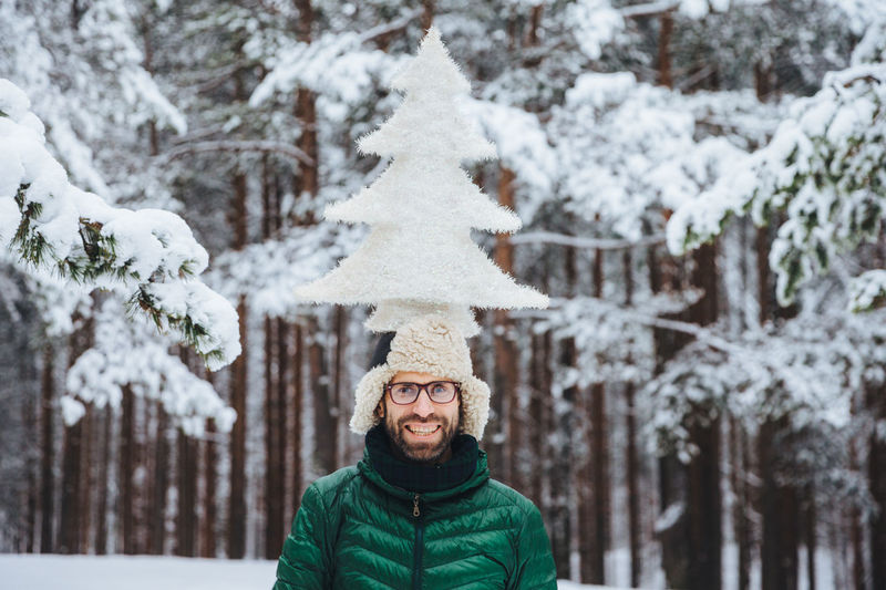 Portrait of smiling woman standing on snow covered tree
