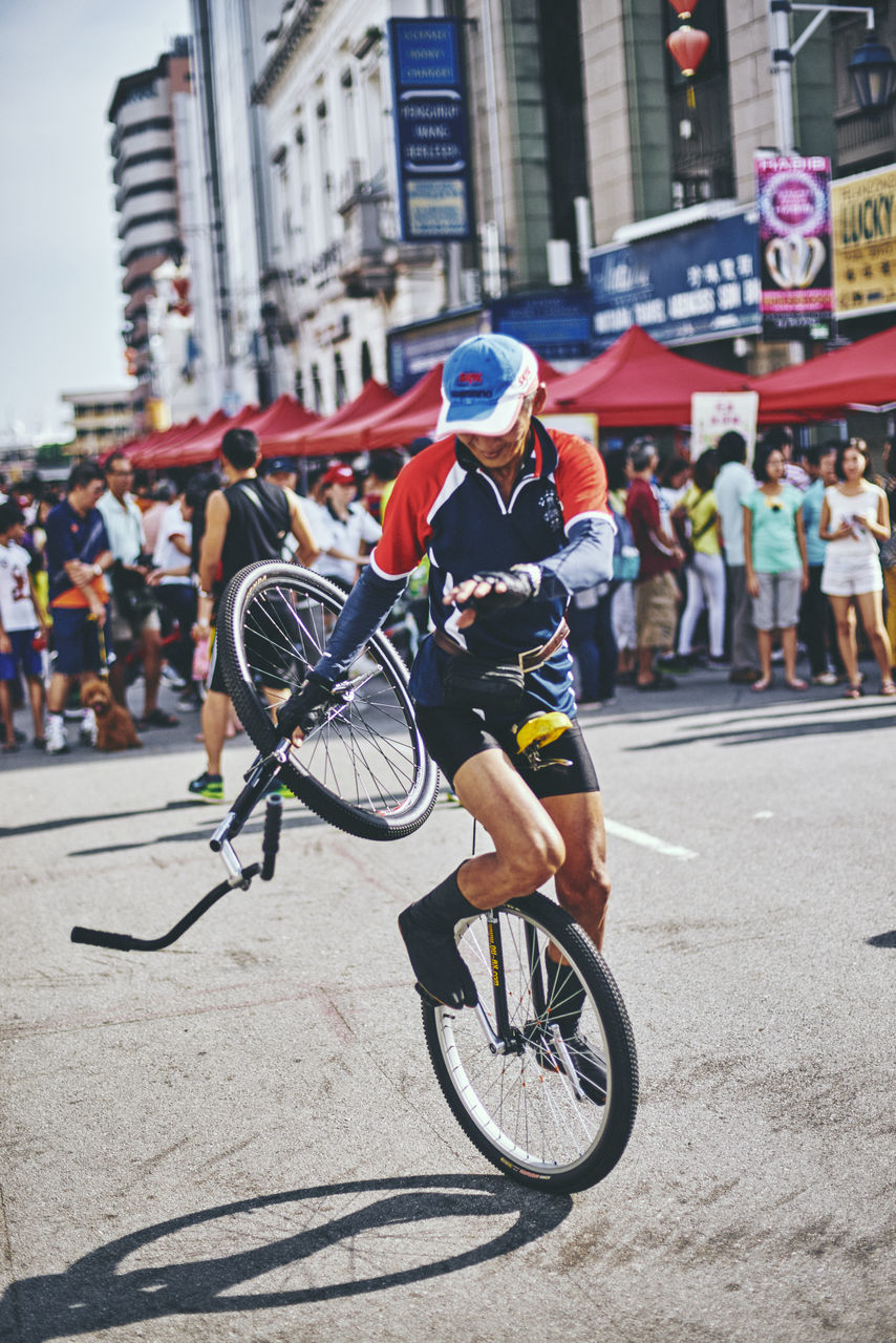 bicycle, cycling, real people, riding, helmet, mode of transport, land vehicle, cycling helmet, transportation, lifestyles, headwear, street, outdoors, city, men, day, large group of people, architecture, building exterior, leisure activity, sports helmet, full length, built structure, women, racing bicycle, road, biker, adult, people