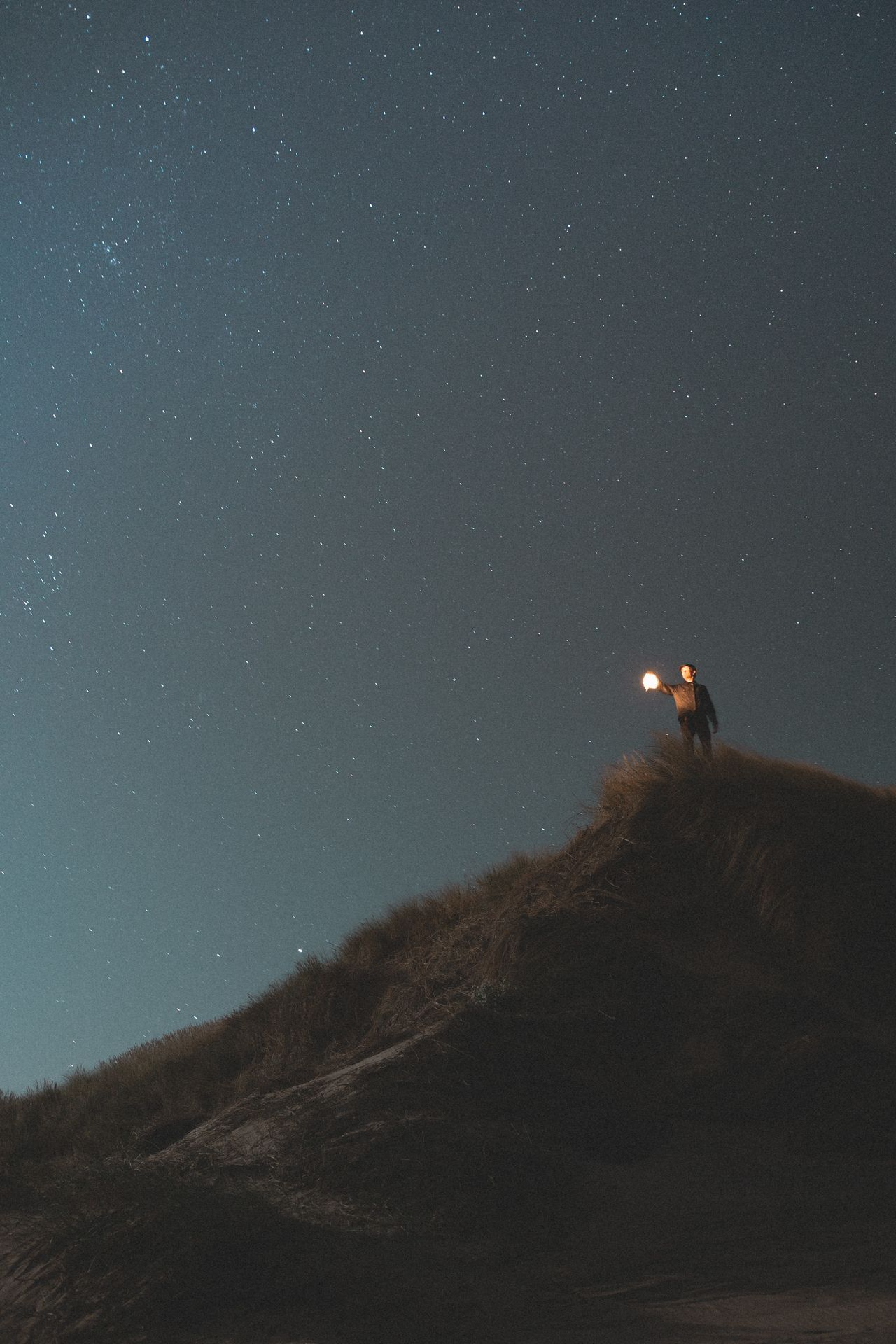 Low angle view of man on mountain against sky at night