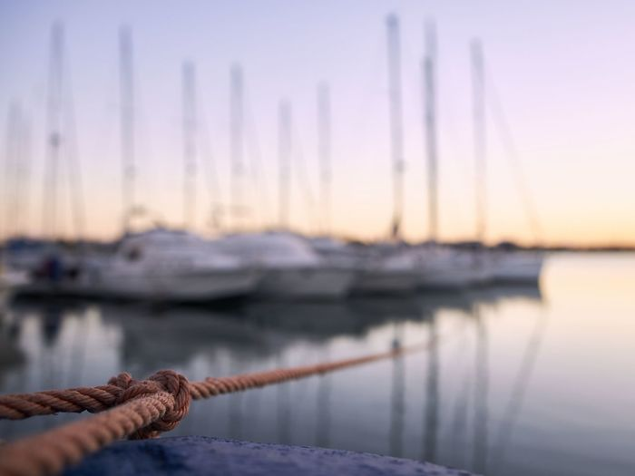 Close-up of rope against sailboats moored in sea at sunset
