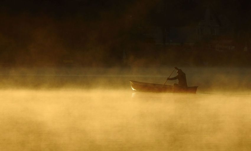 Person Rowing Boat In Lake During Sunset