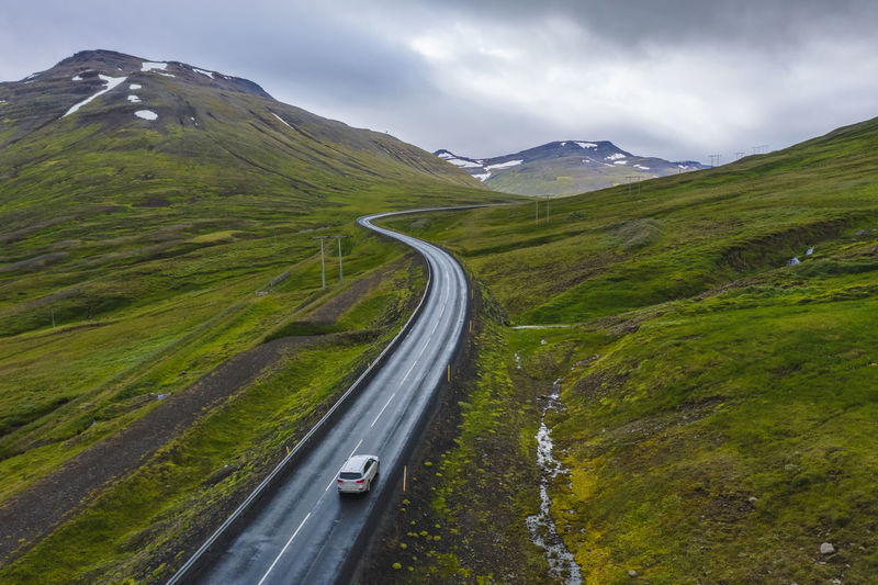 Lonely rent car drive on a remote road with beautiful scenery of iceland.