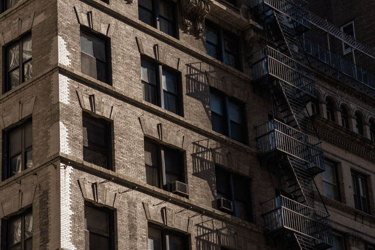 Close-up of apartment block, low angle view Built Structure Window Building Exterior Architecture Low Angle View No People Backgrounds Building Residential District Day Pattern City In A Row Sunlight Repetition Apartment Metal Stairs Escape Stairs New York NYC Light And Shadow Urban Urban Geometry