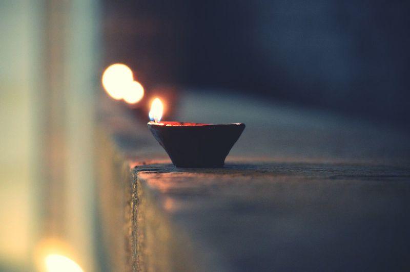 Close-Up Of Illuminated Diya On Table