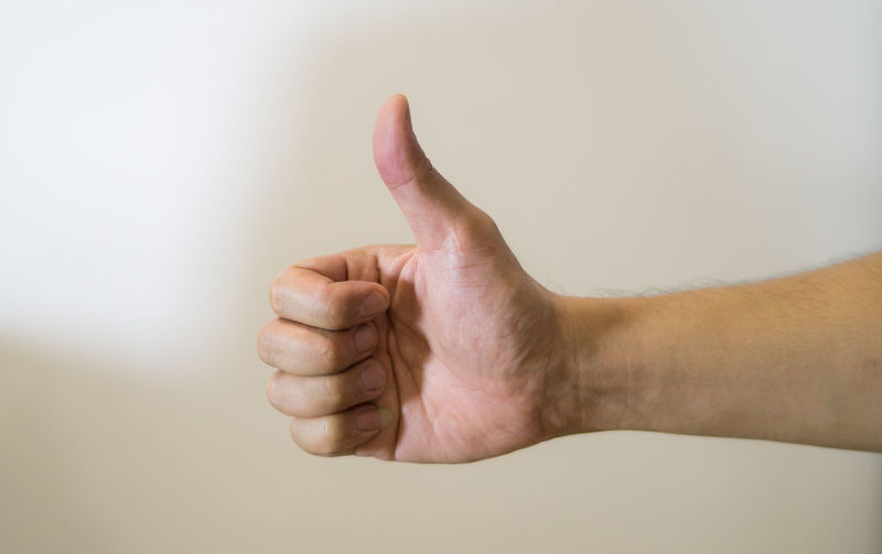 Approval thumbs up like sign as hand gesture isolated over white background Adult, Agree, Agreement, Approval, Approve, Arm, Background, Business, Caucasian, Communication, Concept, Decline, Down, Expressing, Finger, Gesture, Gesturing, Good, Hand, Human, Icon, Idea, Index, Isolated, Male, Man, Number, Ok, One, Palm, Part, Person Human Finger Human Skin Indoors  Lifestyles Part Of Person Personal Perspective Studio Shot Wall - Building Feature White Background