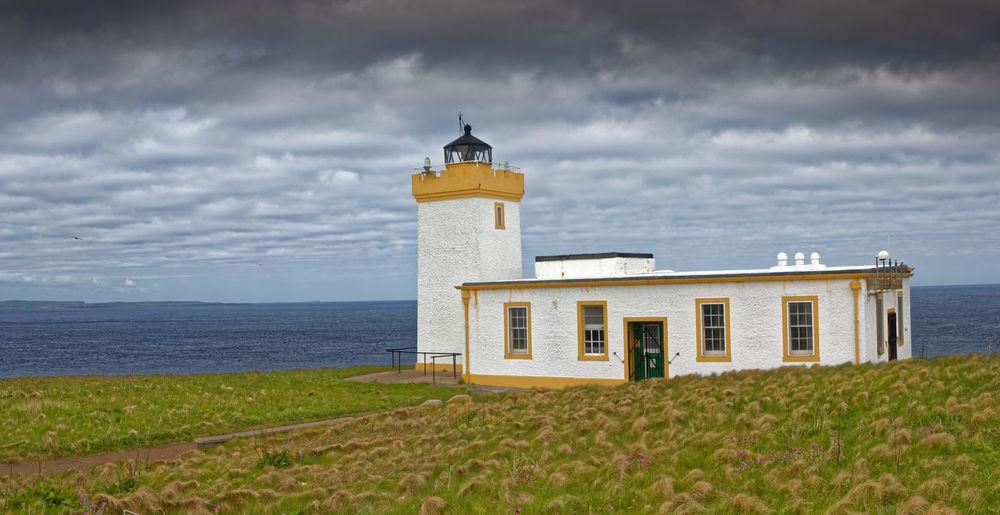 Lighthouse amidst sea and buildings against sky