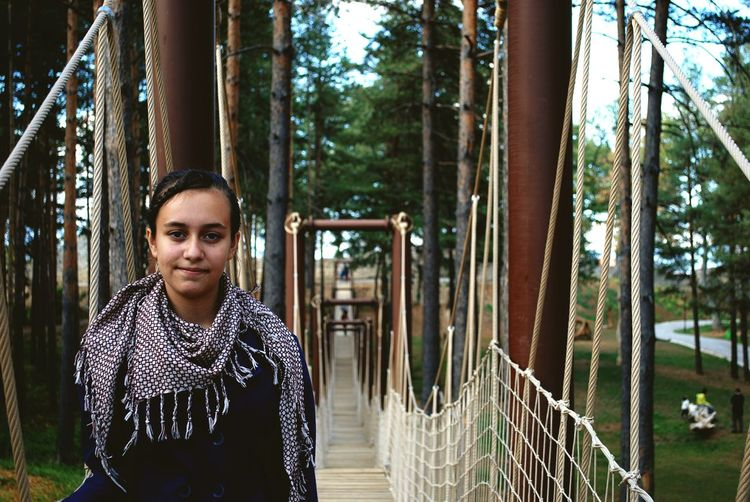 Portrait of young woman standing on rope bridge
